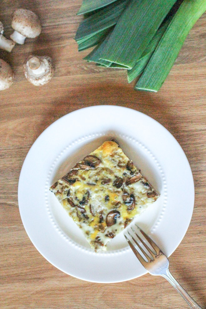 top down view of a square of simple egg bake on a white plate with mushrooms at leeks at top of photo