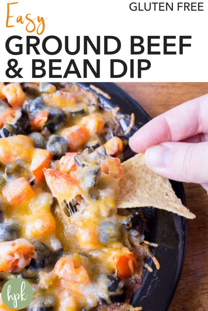 This Easy Ground Beef and Bean Dip comes together in no time, making it a great last-minute recipe when you need something quickly. It's perfect to bring to Super Bowl parties, holiday parties, or just a family gathering. There are only 5 ingredients, from the refried beans on the bottom to the cheesy layer on top. Dip tortillas chips into it and chow down! #glutenfree #beandip #superbowl #easy