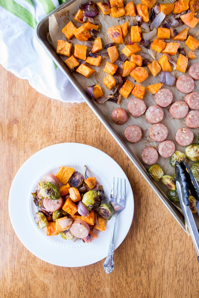 a white plate with sausage and veggies on it, and a sheet pan with the sausage and veggies in top right corner.