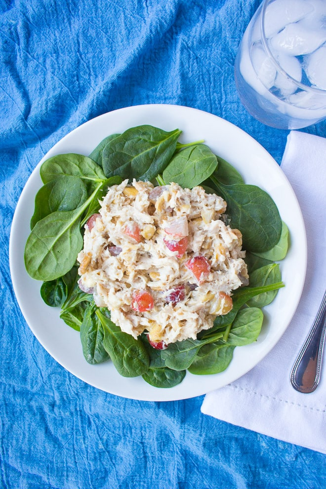 a top down view of cashew grape chicken salad on a bed of baby spinach on a white plate with a bright blue background