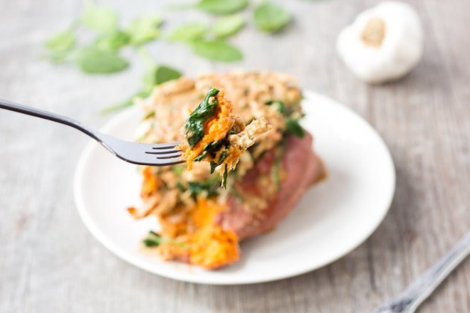 a fork holding up a bite of swimming rama loaded sweet potato with the potato on a white plate in the background on a gray surface with spinach leaves and a head of garlic behind it.