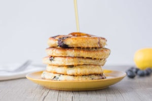 Maple Syrup being poured over a stack of Gingery Lemon Blueberry Gluten Free Pancakes on a yellow plate