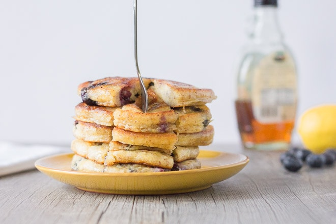 stack of pancakes on a small yellow plate with syrup, lemon, and blueberries in background