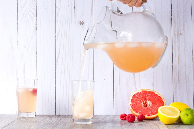 sparkling citrus mocktail being poured from a glass pitcher into a tall clear glass with another glass to the left and grapefruit, lemon, and lime to the right