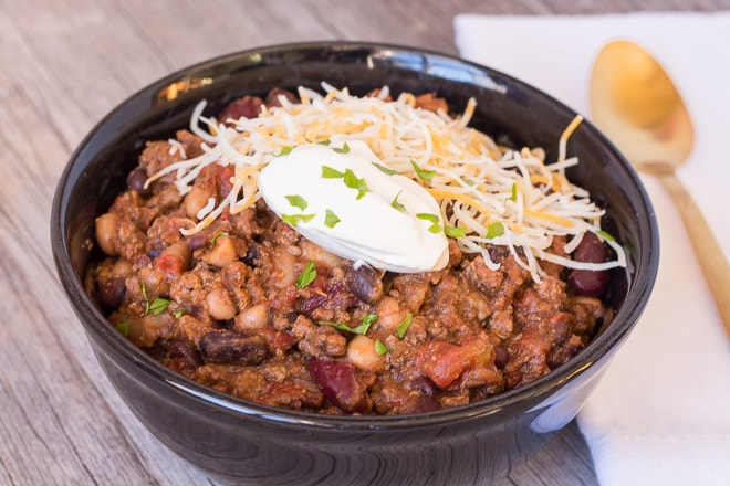 slow cooker beef chili in a black bowl with cheese and sour cream on top