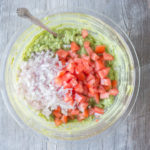 bowl of citrusy simple gucamole with chopped shallots and tomatoes
