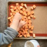 little kids seasoning cubed sweet potatoes in a pan with salt