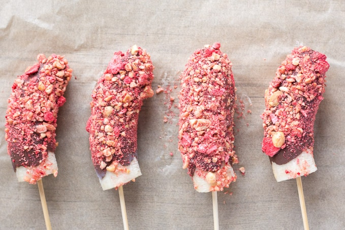 four PB&J chocolate covered frozen banana pops on parchment paper