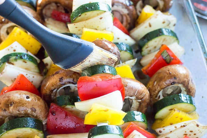 putting the marinade on vegetable skewers for the gluten free teriyaki chicken kabobs