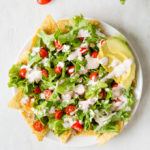 white plate with nachos, lettuce, cut cherry tomatoes, and dressing on top, with slices of avacado on the upper right. On a white background with several tomatoes and some lettuce up top and two tortilla chips on bottom right