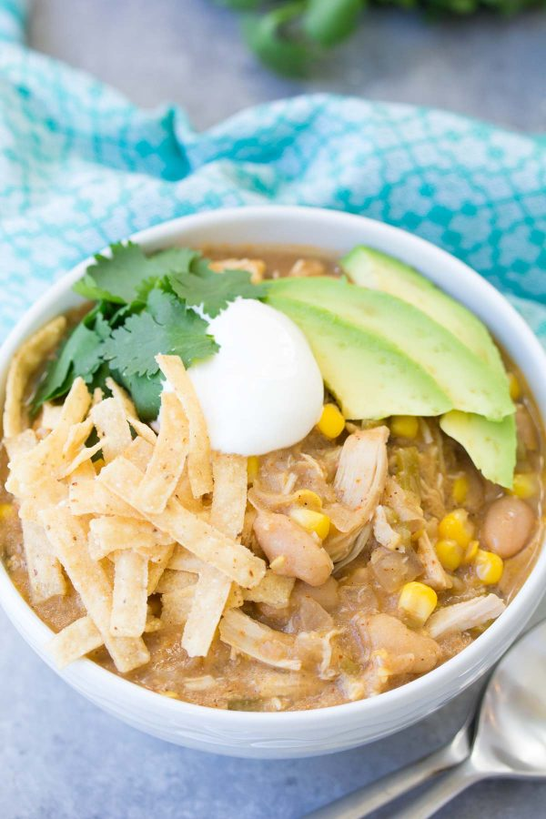 white chicken chili in a white bowl with tortilla chips, avocado slices, sour cream, and parsley. a blue towel is in the background