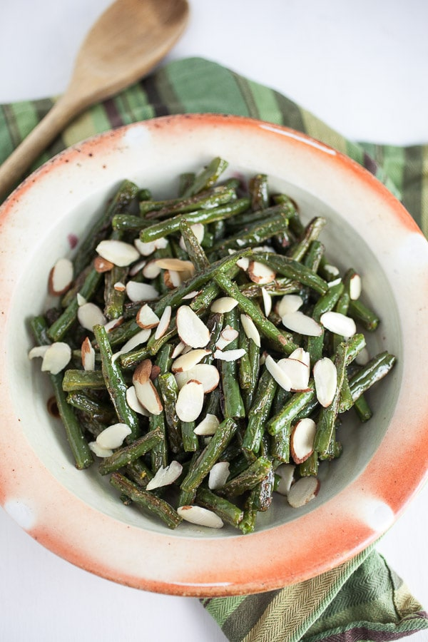 roasted green beens with slivered almonds in a white bowl with orange coloring