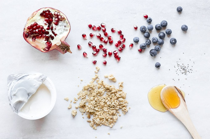 elements of a breakfast yogurt parfait - half a pomegranate with seeds to the left of it and blueberries to the right of the seeds (in the upper right corner). A vanilla greek yogurt container is in the bottom left, with granola to the right and some honey spilled out over a wooden spoon in the bottom left corner. All on a nearly white background, taken from the top down.