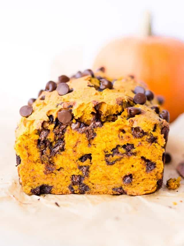 straight on shot of a loaf of chocolate chip pumpkin bread with a pumpkin in the background