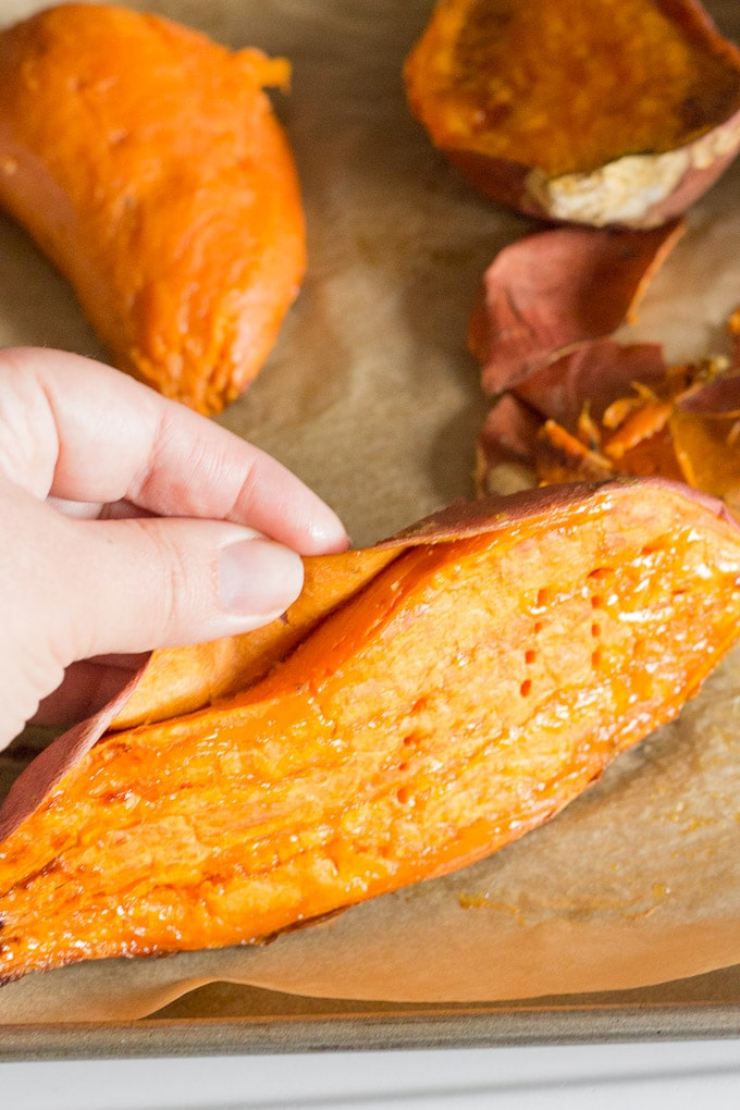 peeling skin off a roasted sweet potato for gluten free sweet potato casserole