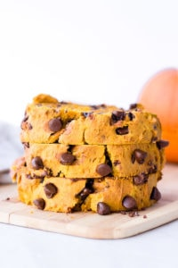 three slices of chocolate chip pumpkin bread stacked on top of each other, on a wood cutting board with a tan napkin and orange pumpkin in the background