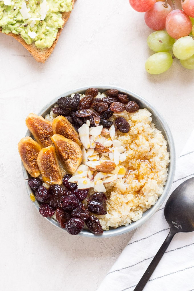 top-down shot of quinoa breakfast bowl with avocado toast in the upper left, grapes in the upper right, and a napkin and spoon in the bottom right.