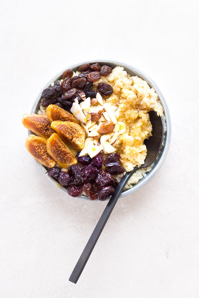 top-down shot of quinoa breakfast bowl with a dark spoon in it on the right.