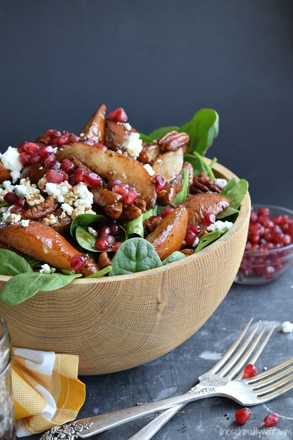 roasted pear pecan salad in a large wood bowl on a dark gray background