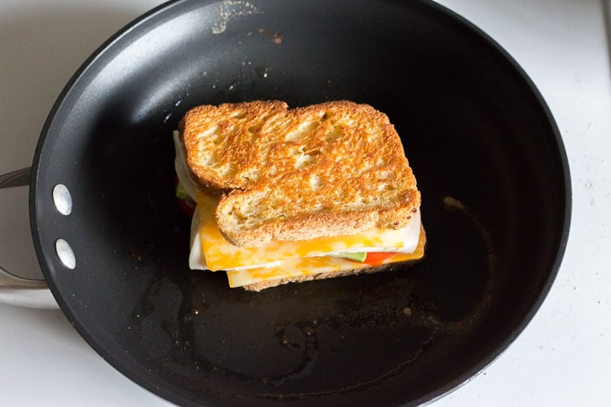 a large non-stick pan with a gluten free grilled cheese sandwich in it