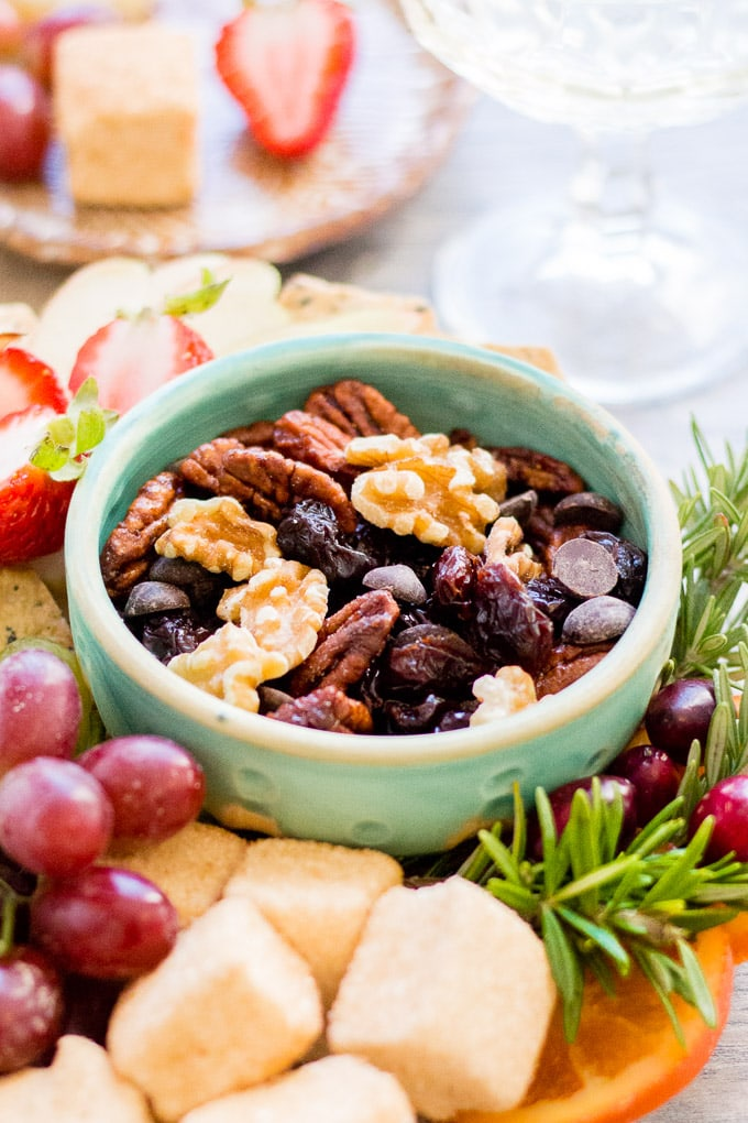 an angle shot of gluten free trail mix in a small teal bowl surround by fresh fruit and other snacks