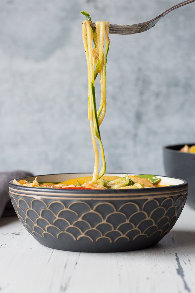 side view of zucchini noodles being lifted out of a bowl of chicken curry zoodles with a fork