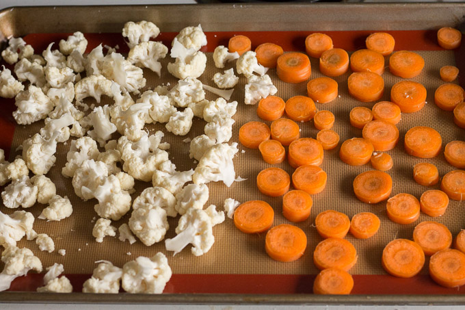 cut up cauliflower and carrots on a sheet pan