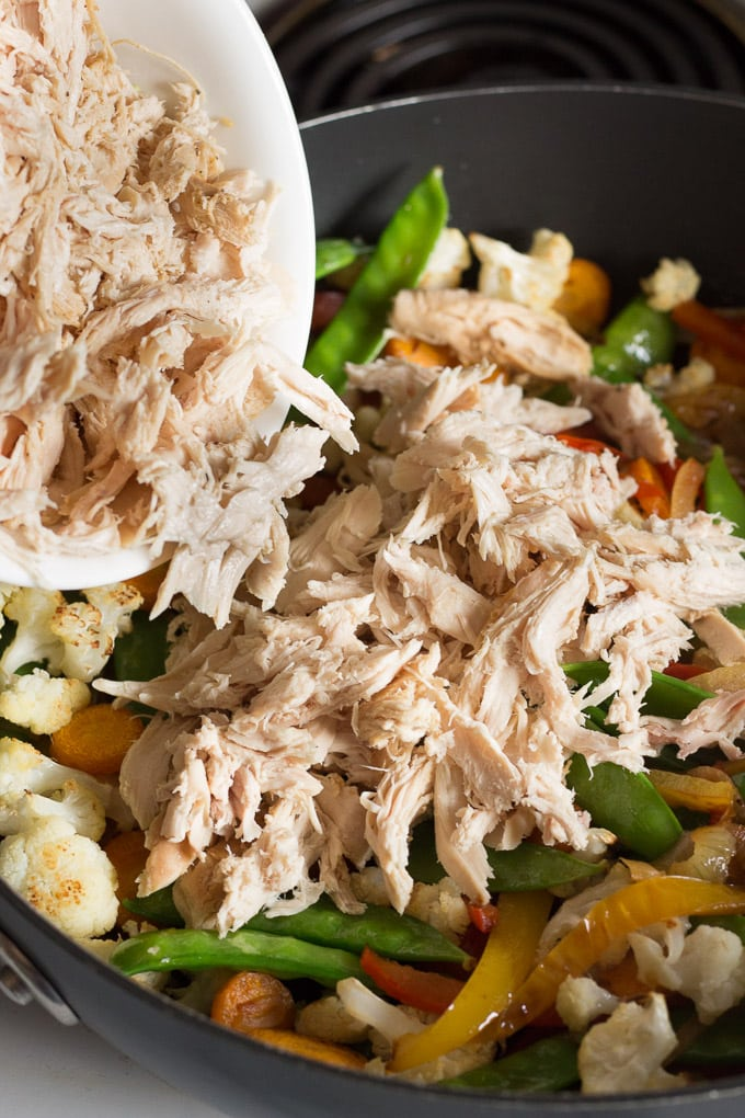 shredded chicken being added to a frying pan with sauteed onions, bell peppers, and snow peas