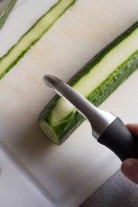 top down view of making cucumber ribbons on a cutting board