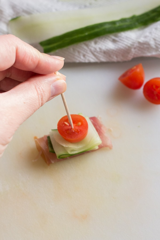 a hand holding a toothpick and pierce a cut tomato, a cucumber ribbon, and some prosciutto together.