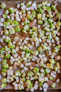 top down view of cubed potatoes and romanesco on a sheet pan