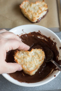a hand dipping a chewy coconut macaroon heart into a bowl of melted chocolate