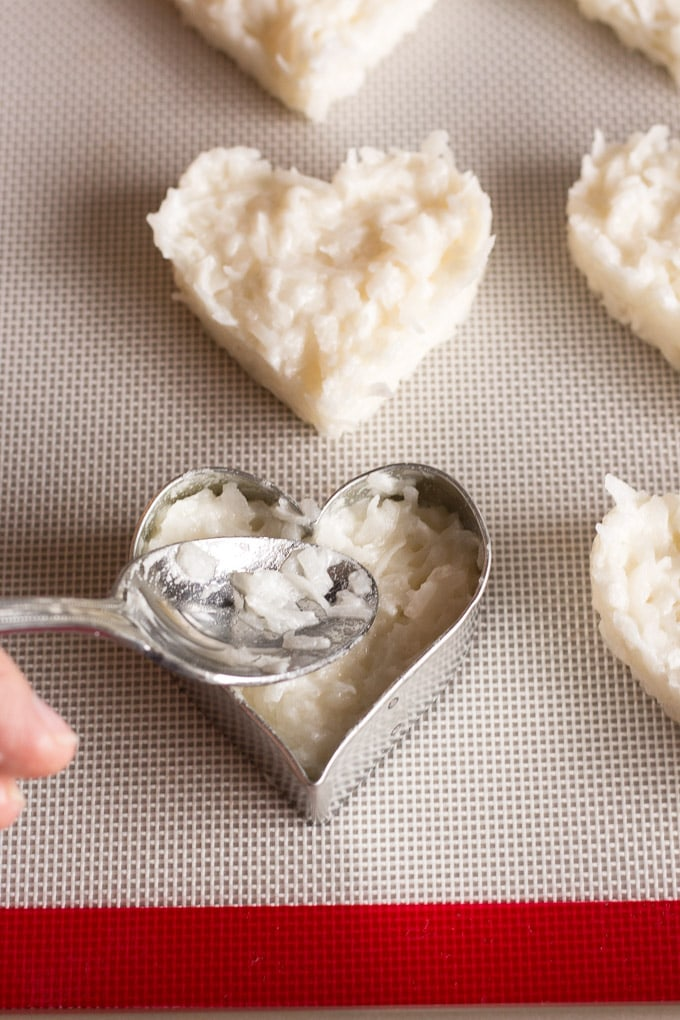 a heart shaped cookie cutter on a silicone mat in a sheet pan with coconut macaroon batter being pressed into it by a silver spoon