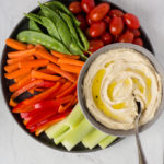 top down view of roasted garlic cashew dip on a plate surrounded by veggies