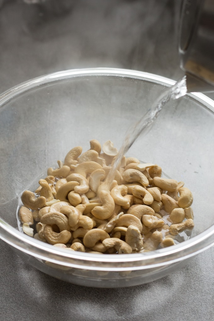 hot water being poured onto raw cashews in a large clear bowl