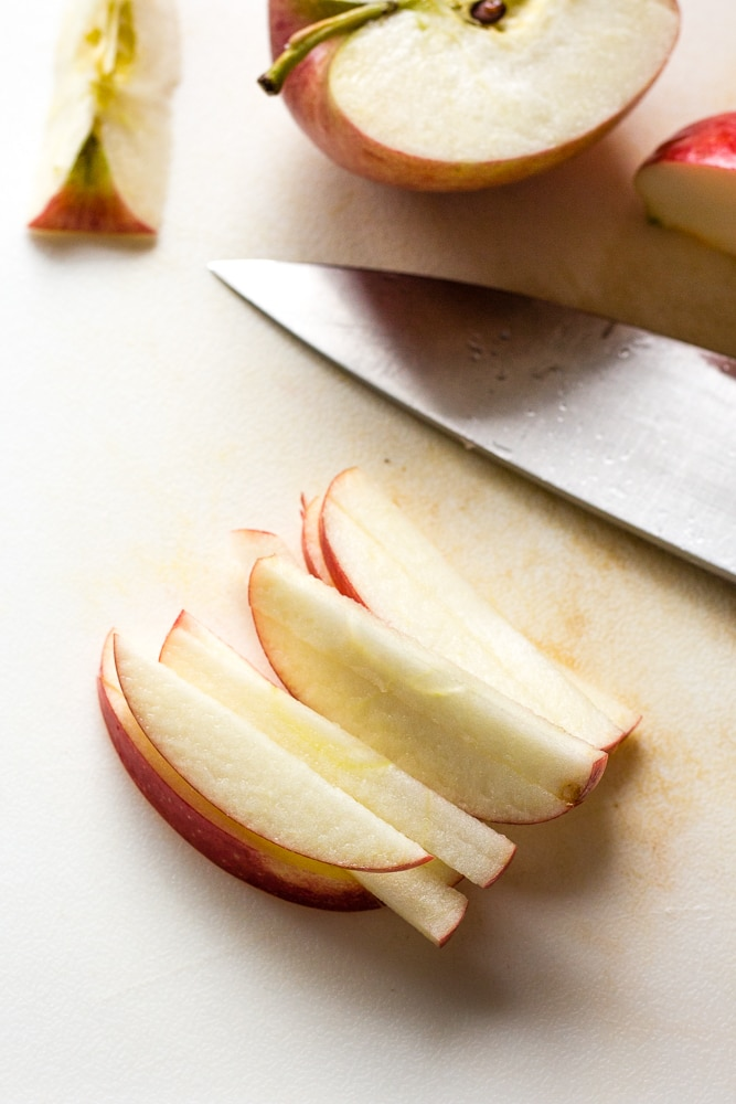 an apple cut into long thin pieces on a white cutting board