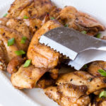 grilled teriyaki chicken thighs being grabbed by a pair of tongs