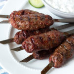 lamb kababs on a white plate with dip in a bowl