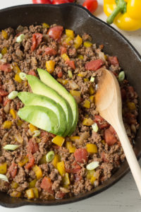 sliced avocado on top of mexican ground beef with a wooden spoon