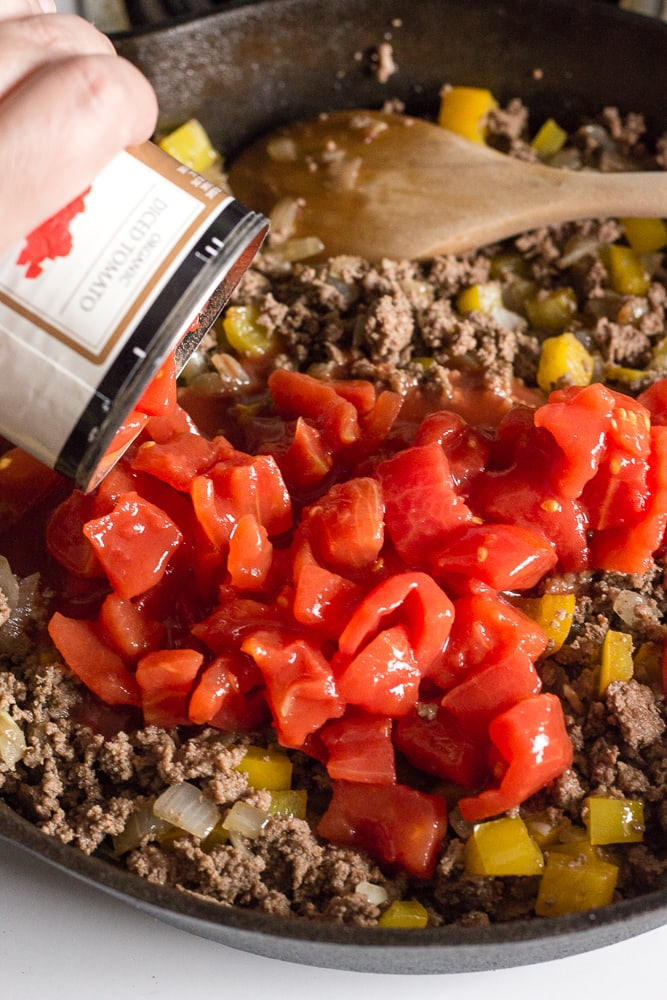 diced tomatoes being poured into cooked ground beef