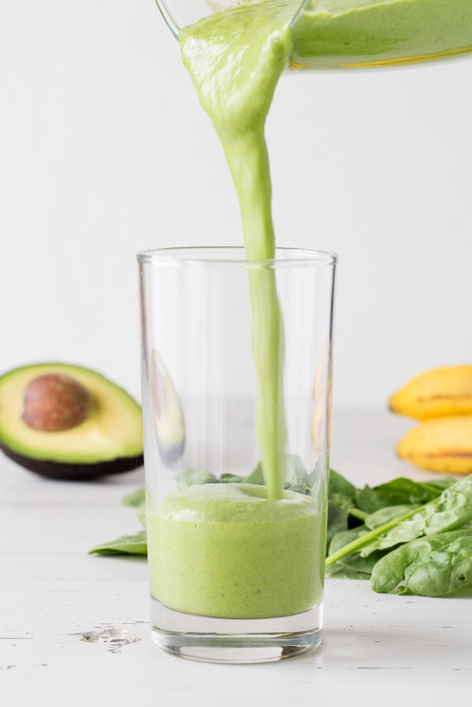 spinach avocado smoothie being poured into a glass