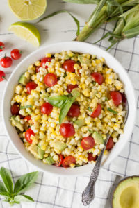 corn tomato avocado salad in a white bowl