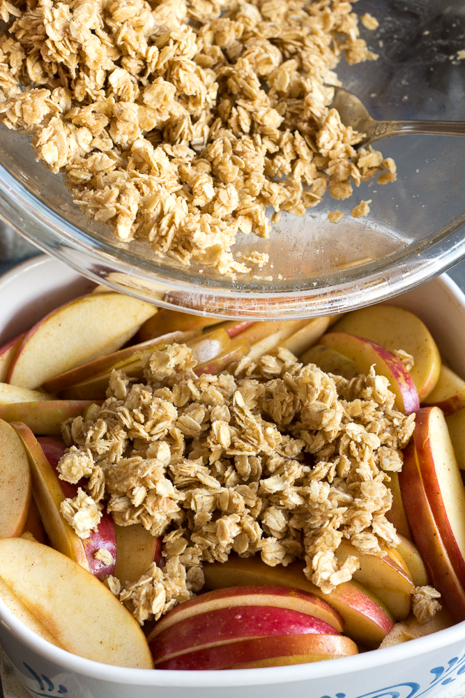 oat topping being put over sliced apples