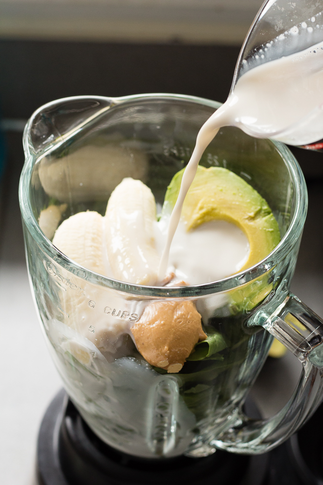almond milk poured over ingredients in a blender