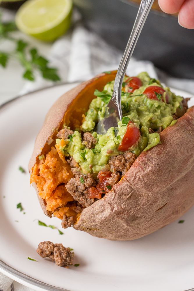 a fork taking a scoop out of a stuffed sweet potato