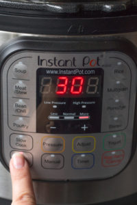 a finger pressing the saute button on an Instant Pot