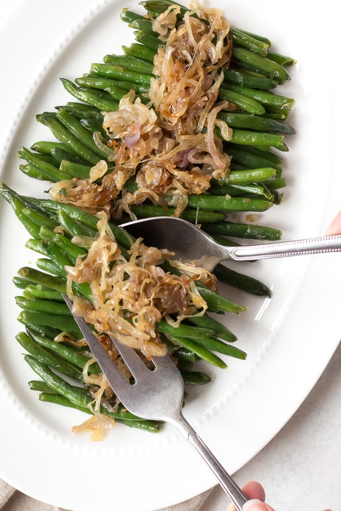 green beans with shallots being dished off a white platter