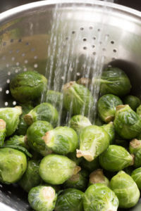 rinsing brussels sprouts in water in a colander