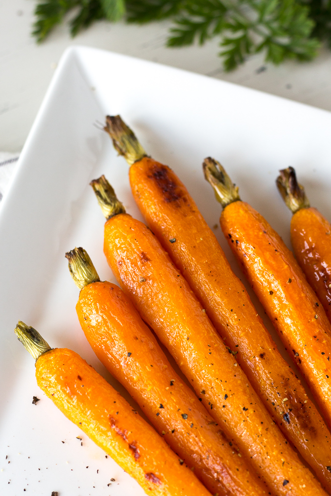 roasted carrots on a white plate with greenery
