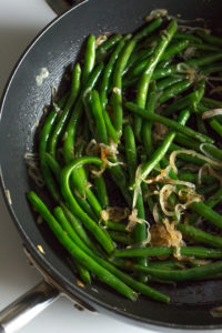 cooked green beans and shallots in a pan